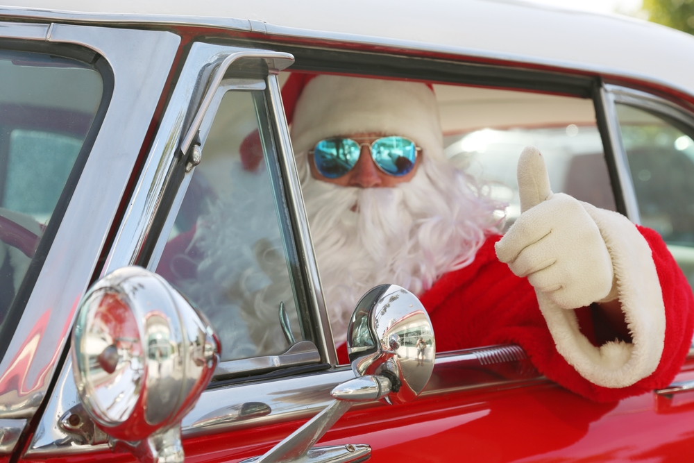 Santa with sun glasses driving car